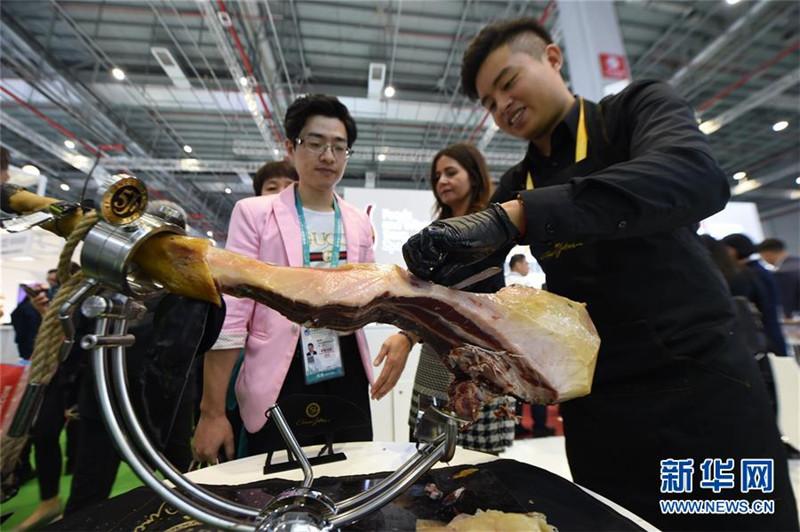 2. 11月6日,在上海举行的第二届中国国际进口博览会上,参观者等待品尝西班牙火腿。 新华社记者 尹炣 摄.jpg