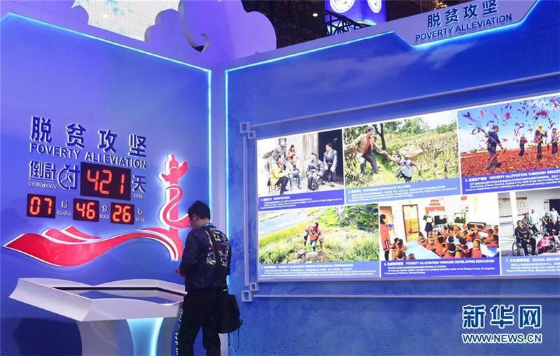 """13. 11月6日,观众在第二届进博会中国馆""""美丽中国""""单元脱贫攻坚倒计时显示屏前参观。 新华社记者 魏海 摄.jpg"""